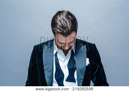 Portrait of a young handsome man in a suit, bow tie and shirt buttons undone, looking down, against plain studio background