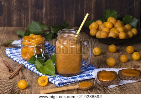 Healthy eating food dieting and vegetarian concept - mug glass of juice smoothie shake from yellow plum jam and ripe yellow plum on a vintage wooden table. Bio healthy food and drink. Organic diet