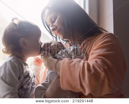 Mother and older daughter enjoy a new family member kissing him on the first morning sunshine