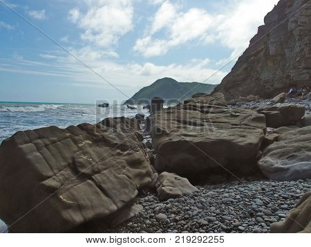 Huge rocks and the sea. You can see the blue sky, waves, and horizon far away. The waves might crash the rocks.