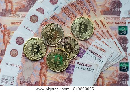 Coins bitcoin, lie on bill of 5000 thousand rubles. The banknotes are spread out on the table in free order. Gold coins are crypto currency.