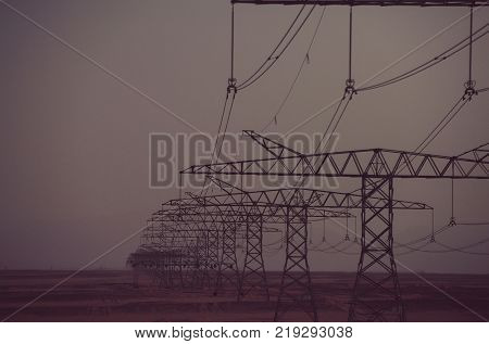 Global warming climate change. Power line towers in desert on dusk sky background. Electric energy transmission. Electricity distribution stations. Ecology eco power technology concept.