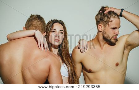 Men with sexy torsos stand with sensual woman on grey background. Erotic desire love games concept