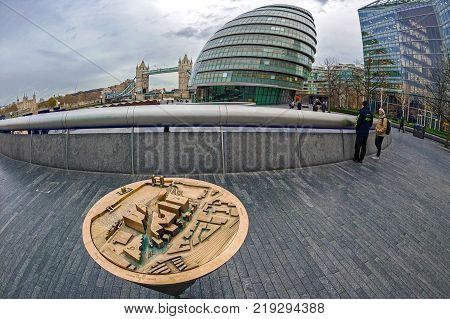 LONDON ENGLAND - NOVEMBER 27 2017: View with London City Map from metal City Hall Skyscrapers Tower Bridge and the River Thames.