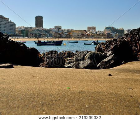 Cove of sand and rocks in foreground, Las Canteras beach and Las Palmas city, Canary islands
