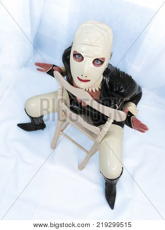 Creepy living doll woman in latex rubber catsuit and hood sitting on a chair viewed from above. Freaky stare with direct eye contact. Background with color filters on white for artistic effect.