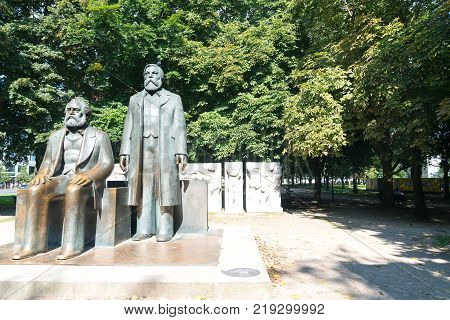 BERLIN GERMANY -AUGUST 28 2017; Statue of two men considered to be the fathers of socialism Karl Marx and Friedrich Engels in park in Berlin.