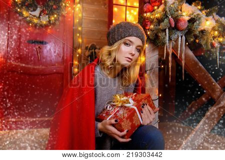 Pretty girl is sitting on the porch of a house decorated for Christmas and holding a gift box. Time for miracles.
