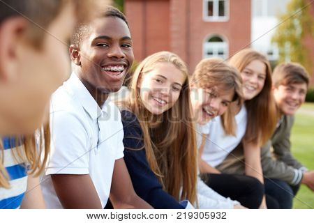 Group Of Teenage Students Sitting Outside School Buildings