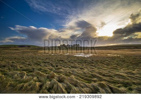 Wind swept grass meadow with Skaill House in the background, Orkney, Scotland.