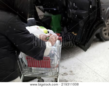 Woman pushing shopping trolley to the car with open door