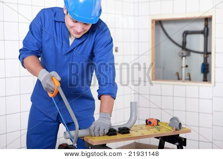 Plumber sawing plastic pipe