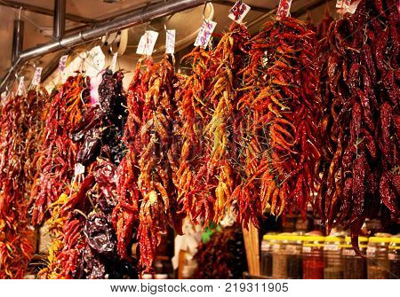 Bunch of red peppers at La Boqueria market in Barcelona, Spain. Hot chilies hung up to dry.
