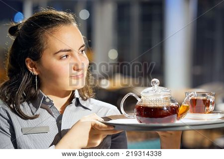The waitress is carrying tea. Hospitable girl waitress holding tray with cup of tea and tea glass teapot in a restaurant. The concept of maintenance and service.