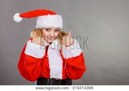 Xmas seasonal clothing winter christmas concept. Happy woman wearing Santa Claus helper costume showing thumb up gesture.