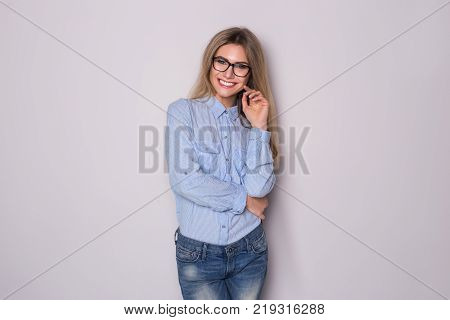 Happy blonde business woman in eyeglasses looking at the camera over gray background.