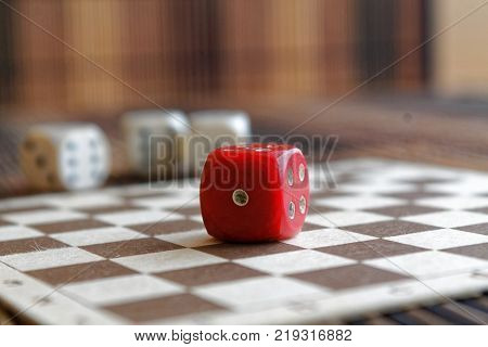 Stack of three white plastic dices and one red dice on brown wooden board background. Six sides cube with black dots. Number 1