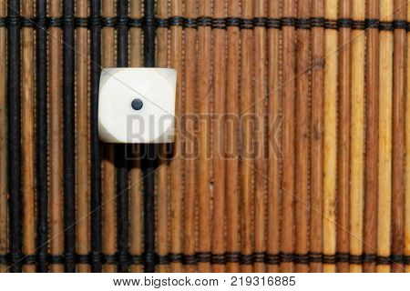 One white plastic dice on brown wooden board background. Six sides cube with black dots. Number 1
