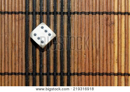 One white plastic dice on brown wooden board background. Six sides cube with black dots. Number 6