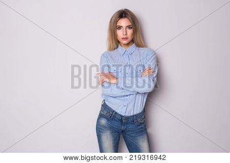 Portrait of serious young business woman looking at the camera isolated on gray background.