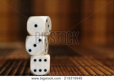 Stack of three white plastic dices on brown wooden board background. Six sides cube with black dots. Number 1 3 6