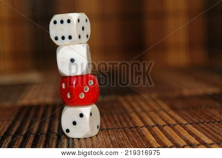 Stack of three white plastic dices and one red dice on brown wooden board background. Six sides cube with black dots. Number 1 3 6