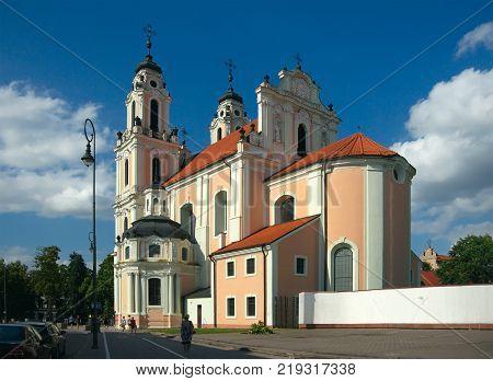 Vilnius Lithuania - August 16 2017: Church of St. Catherine (1650 by Johann Christoph Glaubitz) Vilniaus srtreet and passersby.