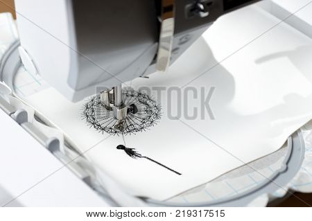 embroidery with embroidery machine - dandilon on white leatherette - view on embroidery process machine head and hoop from left