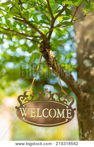 Metal welcome sign hang on tree with bokeh blurred background in the garden