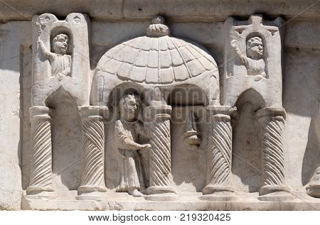 LUCCA, ITALY - JUNE 03: Relief above the portal San Salvatore church in Lucca, Tuscany, Italy on June 03, 2017.