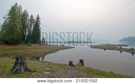 Canyon Creek Campground and partially submerged stumps on the Hungry Horse Reservoir during the 2017 fall fires in Montana United States