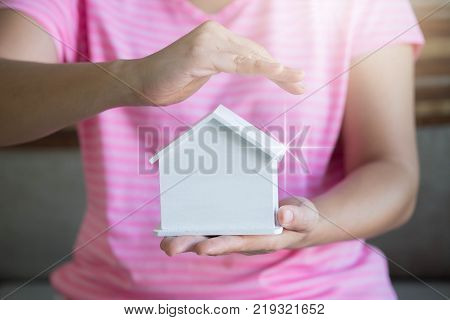 Woman hands presenting a house. Real estate agent offer house. Property insurance and security concept.