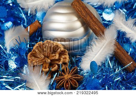 Pines cones cinnamon sticks star anise feather and silvery bauble on a blue tinsel as decoration for Christmas