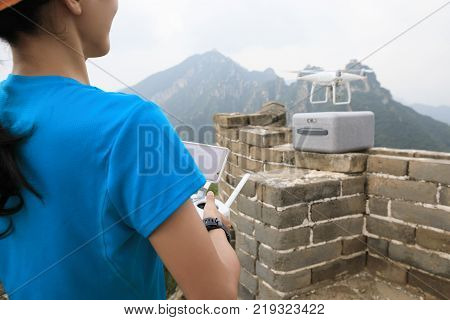 Woman controlling flying drone which taking photo of the great wall landscape in China