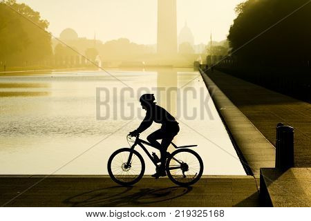The biker silhouette in a misty sunrise as seen from National Mall - Washington DC, United States