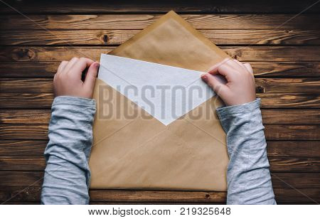 A large brown envelope holds the child's hands. Open envelope on a wooden background. A blank sheet of paper in an envelope. Copy space.