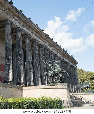 BERLIN GERMANY - AUGUST 28 2017; Exterior colonnade of historic Altes Museum on Museum Island in middle of city with statues of Lion Fighter on horseback by Albert Wolff guarding the entrance steps.