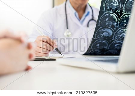Professor Doctor discussion a method with patient treatment with Mammogram film x-ray of patient 's head for brain skull or eye injury and laptop computer on table.