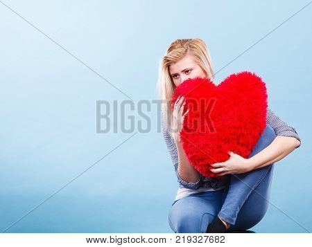 Break up divorce bad relationship concept. Sad depressed woman holding big red fluffy pillow in heart shape she needs love.