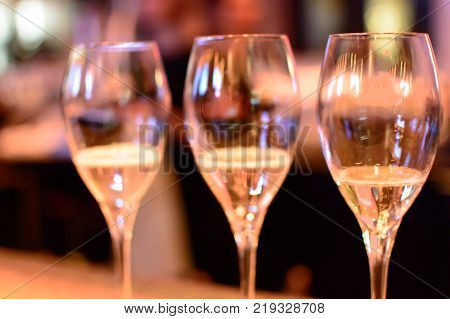 New year's eve celebration with champagne, row of champagne glasses and flutes with sparkling wines and champagne ready to drink in a row with sparkling light closeup holiday New Year's eve and New Years day conceptual photography