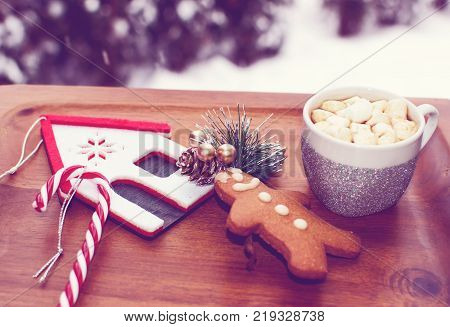 Cozy winter solstice background, falling snow with Winter hot drink. cute Christmas or winter vacation hot chocolate or cocoa with marshmallow on rustic vintage wood tray with christmas decorations candy cane, traditional gingerbread man holiday happiness