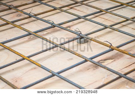 Rebars steel wire mesh which is supported by mortar cover box and wooden plate for precast concrete flooring on construction site selective focus.