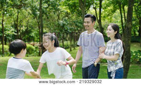 Asian family enjoying summer weekend in park walking & smiling