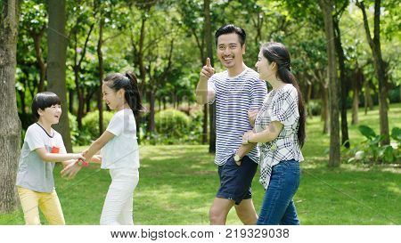 Asian family laughing & walking in park in summer