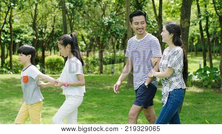 Chinese family walking in natural park in summer smiling and looking at each other