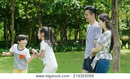 Asian parents smiling & looking at kids playing in park in summer