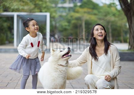 mother and daughter laughing & playing with dog outdoor in garden