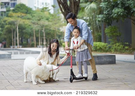 Asian parents & daughter playing scooter while walking dog in garden