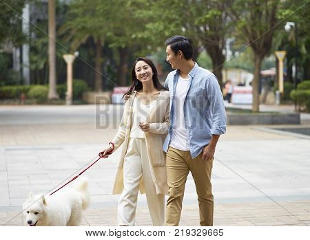 Asian couple laughing while walking dog outdoor in garden