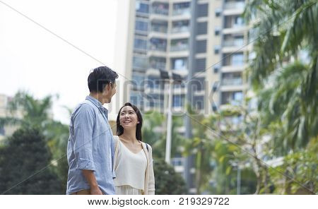 Asian couple standing outdoors in garden looking at each other and smiling